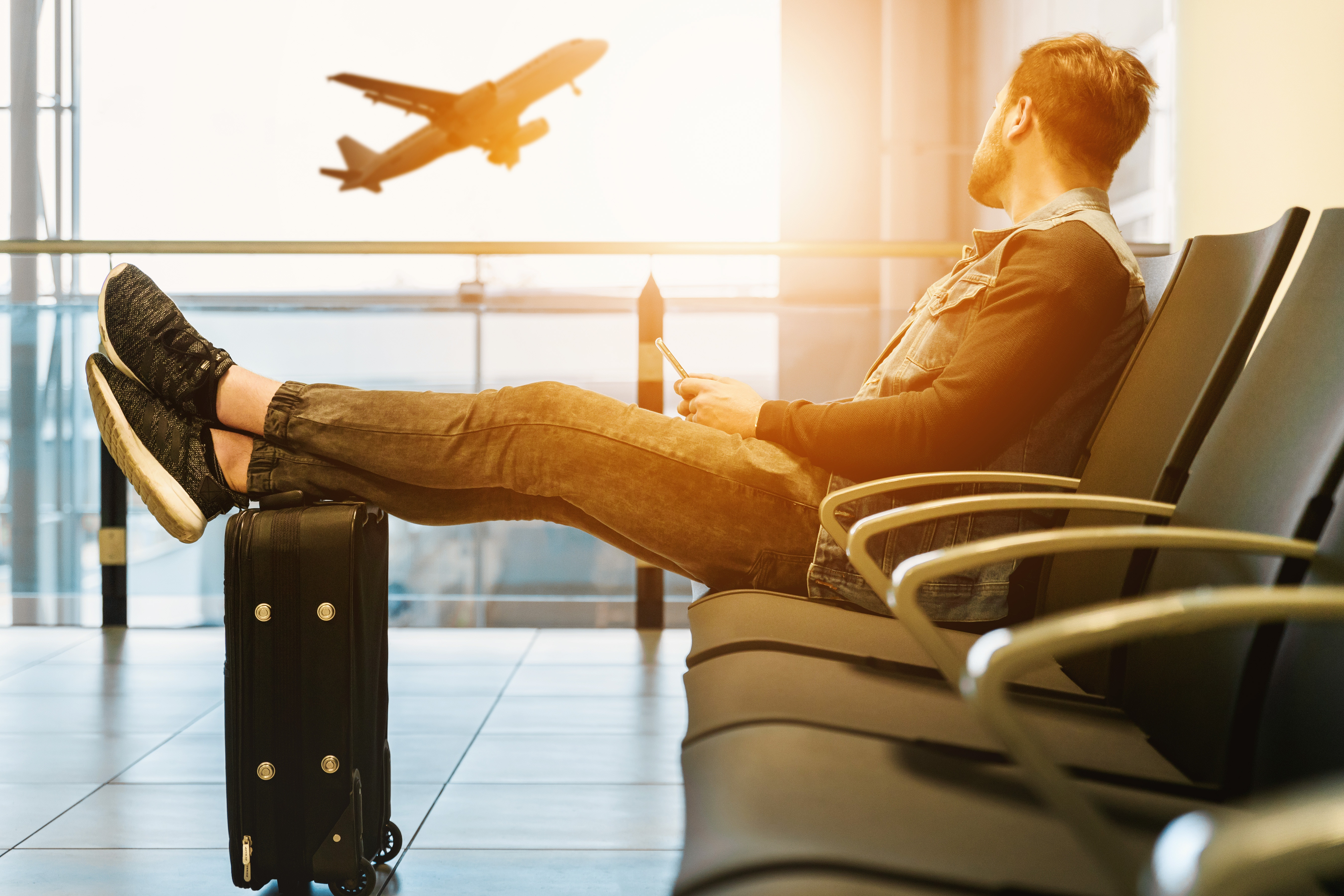 man sitting in airport chair looking out the window at airplane